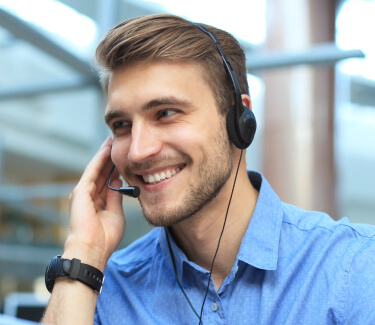 Male receptionist in blue shirt wearing headset